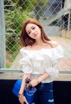 She keeps her look fresh and basic by pairing dark denim jeans with a contrasting white off-shoulder blouse. Her cobalt blue clutch goes perfectly too. Very pretty. -Lily. #streetstyle