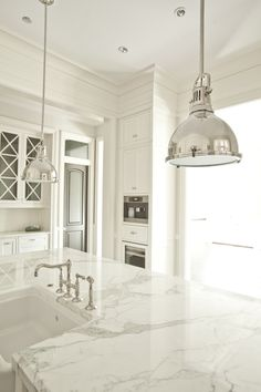 White Marble Kitchen Island, Cabinets, Floors, and Modern Industrial Nickle Lighting, by PLD Custom Home Builders.