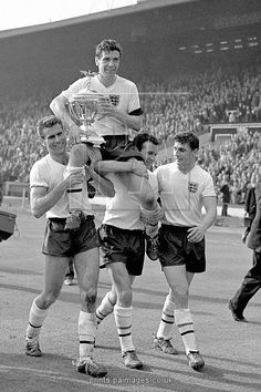 England captain Johnny Haynes (c), keeps a tight grip on the British Championship trophy as he is chaired by teammates Peter Swan (l) and Jimmy Armfield (second r) following England's 9-3 victory