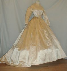 """1860s candlelight satin two piece dress; piping at neck, armscyes & waist, bodice lined with cotton & has front pearl button closure; skirt has long train, lined with silk & buckram, no underarm discoloration or splits; bust: 34""""; waist: 23; skirt length: 43""""-60"""""""