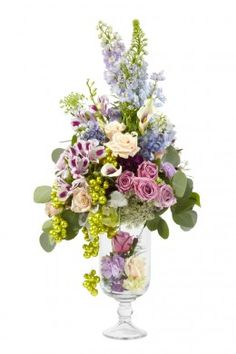 A tall arrangement of lilac blue and white flowers in a glass vase, accented with green beeds