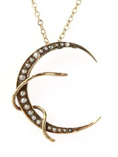 A snake wraps itself around this 14K yellow gold crescent moon. The moon is adorned with graduating seed pearls. From D. Jo.