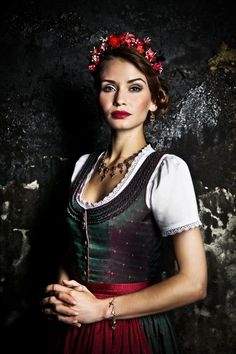 Dark green and red dirndl, with matching flowers in the hair.