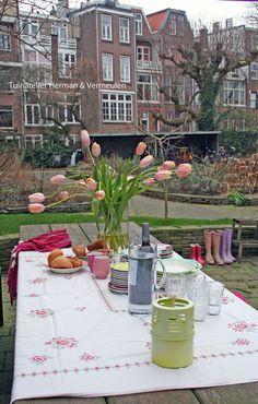 Aan de grote gemeenschappelijke tuintafel kan worden gegeten, gespeeld en de krant worden gelezen. Gemeenschappelijke tuin 'De Omscholing' Rotterdam. Ontwerp Marilene Vermeulen van Tuinatelier Herman & Vermeulen.