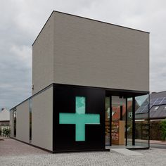 Pharmacy M by Caan Architecten {A cross-shaped window in the sliding door of this Belgian pharmacy transforms into a green sign during opening hours.}