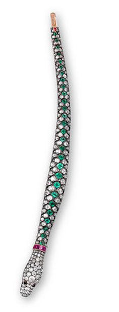 An antique diamond and gem-set bracelet, circa 1890 in the form of a snake, set throughout with old mine-cut diamonds, accentuated by a fancy-shaped emerald spine, square-cut ruby collar and round cabochon onyx eyes; estimated total diamond weight: 11.00 carats; mounted in silver topped gold.