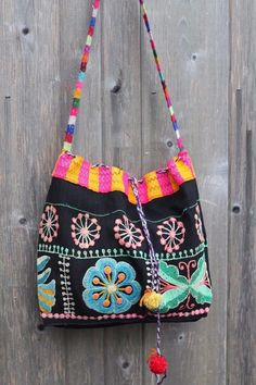 Traditionally, indigenous women in Peru wear many layers of colorful embroidered skirts which they make themselves. When the skirts wear out, they save the embroidered fabric to reuse - in this case, it's been crafted into a fun, unique shoulder bag.   eBay!