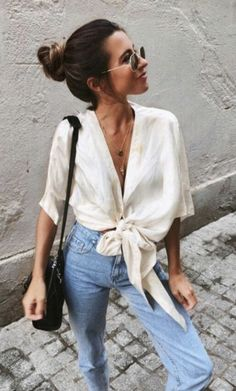 Women's street style: white wrapped tied blouse, high waisted mom jeans, vintage wash, top knot, round sunglasses and black leather purse. Great fall outfit inspiration! #falloutfit #womensstyle