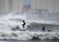 Surfistas pegam onda no litoral da cidade de Brigantine, Nova Jersey. Uma forte tempestade deixou o mar agitado na região