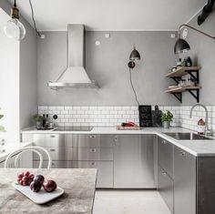 Cozinha no estilo escandinavo com paredes em cinza e armário com acabamento em aço inox.