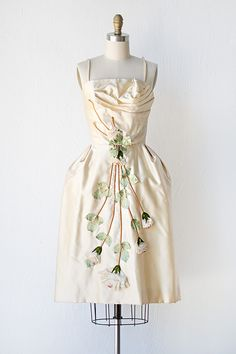 1950s dress made from a cream colored satin with floral applique detail.