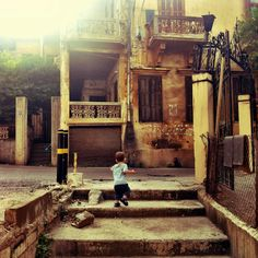 Baby Cole plays outside in the yellow glow of the sun, Beirut, Lebanon.