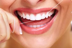 close up of woman flossing white teeth