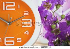 Orange wall clock and Flowers on a wooden table. - stock photo