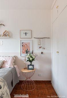 Quarto de casal com meia parede pintada de rosa claro tem prateleira acima da cama com quadros e plantas, almofadas estampadas, carrinho de metal como criado-mudo e violão.