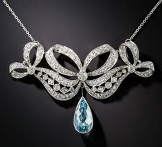 From La Belle Époque, flowing diamond-studded ribbons are neatly tied into a glittering bow in this exceptionally sweet and lovely Edwardian jewel, circa 1910-20s, supporting a deep sky blue colored slender pear-shaped aquamarine swinging below. This refined yet festive necklace is handcrafted in platinum and artfully incorporates open space to accentuate the curvaceous and highly detailed design. 3 carats total diamond weight.