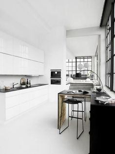 zwart witte keuken met houten bar en zwarte barkrukken