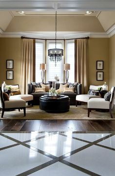 A formal living room with glossy hardwood floors, recessed ceiling with hanging chandelier, and a bay window. Design by http://janelockhart.com/