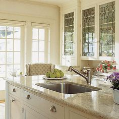 offwhite cabinets, tan counters, stained glass doors, sink in the island, silver hardware, french doors leading to backyard
