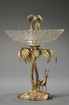 Victorian Gilt-metal and Cut Glass Centerpiece, England, possibly Elkington & Co., Birmingham, cast as a stag on rocky, shaped base beneath a palm tree with a diamond and fan pattern cut glass bowl amidst its fronds.
