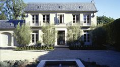 William Hefner Lovely modern French home exterior with white stucco, gray shingles and attached garage.