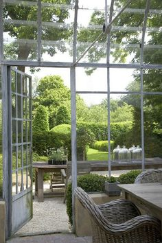 Love it all. The beautiful glasshouse, the old table and cloches and gorgeous green topiary in background.