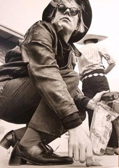 Awesome shot of Andy Warhol showing his cool stacked heel shoes, broken-in leather jacket, and iconic hair framed by a fedora or other kind of jaunty hat. He may be in Mexico.