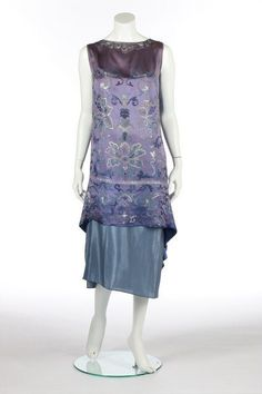 A Callot Soeurs embroidered orientalist cocktail dress, 1926. Photo Kerry Taylor Auctions.  un-labelled, embroidered in floss silks in shades of blue and white with Chinese-style flowerheads and foliage, with draped, pointed rear skirt panel; together with a pale blue silk petticoat, bust 92cm, 36in