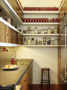 wood lowers, slate counter and floor, white walls and a mix of white upper shelves with a few wood concealed shelves, opposite wall is all wood built in (with stove, fridge, etc.), and under cabinet lighting.