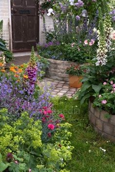 Beautiful cottage garden... looooove the old stone wall and the stone path way too!!!!!!