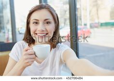 In a good mood. Gorgeous smiling woman making a selfie while having a cup of coffee