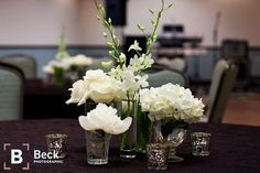 Floral for the reception included white hydrangea, roses, tulips, peonies, calla lilies, ranunculus, and dendrobium orchids arranged in apothecary jars and etched glass vases. Mercury glass candle votives were added to illuminate the room.