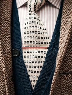 contrasting patterns on tie w/pin striped shirt, tie bar and sweater and sport coat layered look