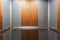LEVELe-105 Elevator Interior with customized panel layout; panels in Bonded Aluminum with Natural Patina and Rain pattern, American Walnut wood veneer, and Stainless Steel with Sandstone finish; Round handrails at Riverside Centre, Portland, Oregon