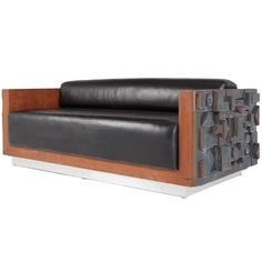 Limited edition, handcrafted sofa by Lou Ramirez for Dex Hamilton. Black vinyl cushions are encased by vibrant wood frames, bookended by abstract Brutalist designs and a stylistic, manufactured patina. Elevated by a base with light metal laminate.    The Brutalist movement of the 1950s, 1960s and 1970s stemmed from a post-war surge in the usage of raw, unrefined materials and pioneered by such influencers as Paul Evans, Silas Seandel, C. Jeré and Laurel. Much like the original designs of…