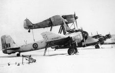 A Focke–Wulf Fw 190 / Ju 88 combination known as the Mistel (Mistletoe) in the snow, likeley in Great Britain after the war. Both aircraft wear Royal Air Force roundels as well as a captured Ju 52 in the distance. The bottom Ju 88 bomber would normally have a cockpit area filled with explosives and a long proboscis-like nose that would detonate the warhead. Photo: RAF