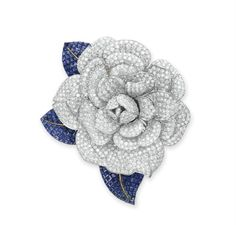 A DIAMOND AND SAPPHIRE FLOWER BROOCH   Designed as a pavé-set diamond camellia blossom, extending three square-cut sapphire leaves, mounted in white and yellow gold