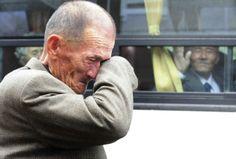 Человек из Северной Кореи (справа) машет рукой из автобуса плачущему южнокорейцу после семейной встречи у горы Кумганг, 31 октября 2010 года.Их разлучила война 1950-53 годов.  И