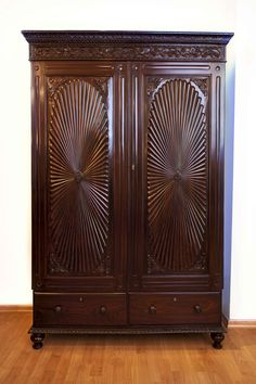 #BritishColonial A British colonial rosewood cupboard with Fleur-de-Lys carving on the frieze. The floating panels of the doors are carved with a large oval sunburst design, centred with an oval disk and leaf embellishments in the  corners. The sunburst or Surajmukhi is a typical motif of the state of Gujarat signifying prosperity. A great example of an early 19th century Anglo-Indian cupboard: generally European in form its decoration was influenced by Indian traditions.