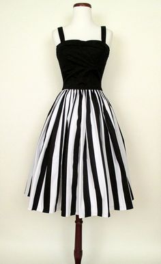 This adorable skirt conjures up images of 1950's Paris, with pretty girls wearing strappy sandals and cute pixie hair cuts strolling the French Quarter. This 1950's inspired gathered skirt features bold vertical black and white stripes on cotton poplin fabric.  Pair this skirt with our black Lauren Blouse or bustier top for a chic retro look! Dry clean only. Made in the U.S.A. by Pinup Girl Clothing      Size Chart      Size bust waist hips   XS       small   26-27  open   medium   28-29…