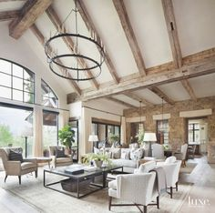 Iron Chandelier High Ceiling Room with Arched Windows with Wooden Beams and Stone