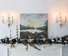 A Wintery Scene: Frame a favorite piece of artwork with matching seasonal items for Christmas. This winter landscape painting shares the mantel stage with silver tree toppers and a garland of greenery and pinecones. Blue and silver ornament picks tucked in amongst the garland complete the look.