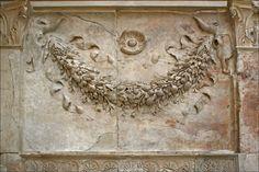 Ghirlanda di primizie - motivo decorativo dell'Ara Pacis che allude al sacrificio che veniva fatto sugli altari arcaici