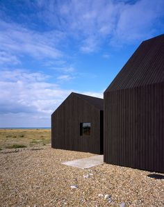 Black stained house is made of three adjoining cabins, each with gabled profiles