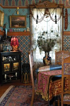 An ebonized cabinet with painted Aesthetic storks sits in one corner of the dining room; swags and a cornice over the vintage lace panels make a lovely window treatment.The Queen Anne house on a corner lot in Portland is transitional, not High Victorian, as it was built after 1900. Still, the wide veranda encircles a tower; its rooms boast pocket doors and plate rails.