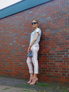 SHADES OF K by Karen  wearing blush pink trousers with side stripe, a grey v-neck t-shirt, nude heels,  silver earrings, stacked bracelets, oversized grey clutch, and black oversized sunglasses.