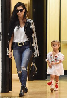 Effortlessly stylish: Kourtney wore a white T-shirt and distressed jeans with shiny black ankle boots and a heavy black leather belt which featured a big silver buckle
