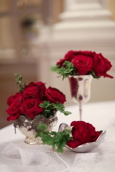 Red rose floral centerpieces in antique silver vases (Photo by Jen & Ashley Photography)