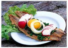 """""""Sol over Gudhjem"""" open sandwich. Smoked herring on rye bread, with raw egg yolk, radishes, chives and onions. The national dish of the island of Bornholm in the Baltic Sea."""