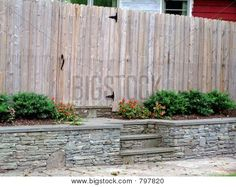 Picture or Photo of Wooden privacy fence along street, with stone retaining wall and steps. Stone Retaining Wall, Fences, Landscaping, Backyard, Outdoors, Exterior, Google Search, Street, Wood